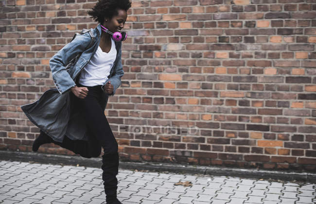 Smiling young woman with headphones and backpack running on pavement — Stock Photo