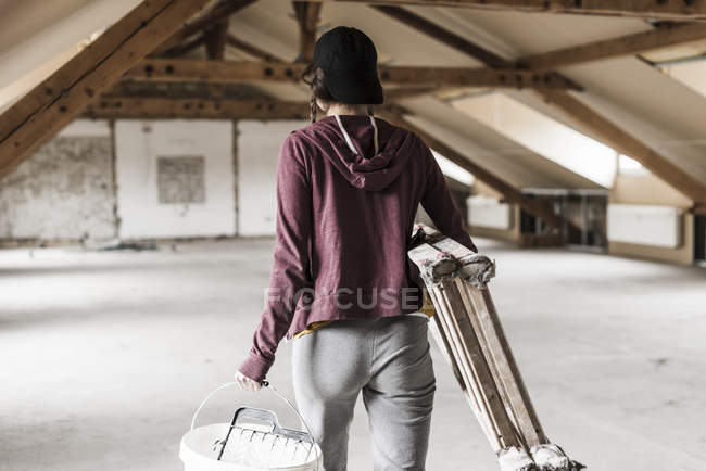 Rear portrait of young woman carrying ladder and bucket — Stock Photo