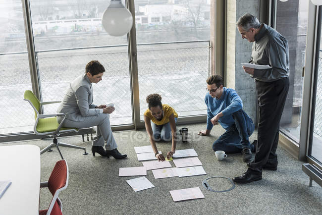 Portrait of business colleagues sorting documents on floor — Stock Photo