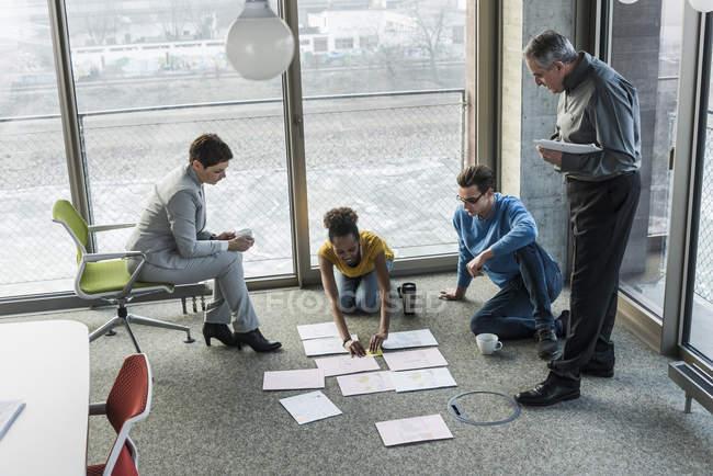 Портрет коллег по бизнесу, сортирующих документы на полу — стоковое фото