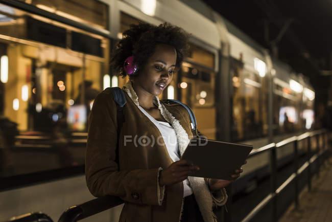 Молодая женщина в наушниках и планшете ждет на остановке трамвая — стоковое фото