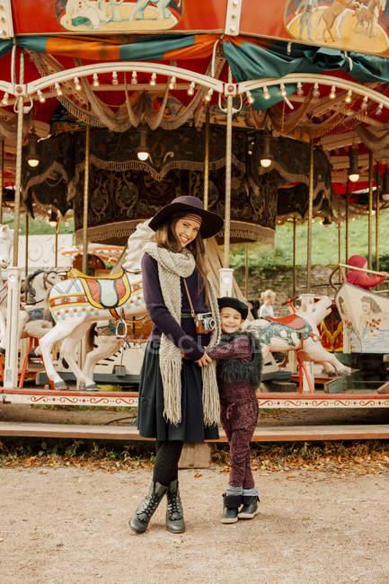 Mulher de pé com a menina na feira e olhando para a câmera — Fotografia de Stock
