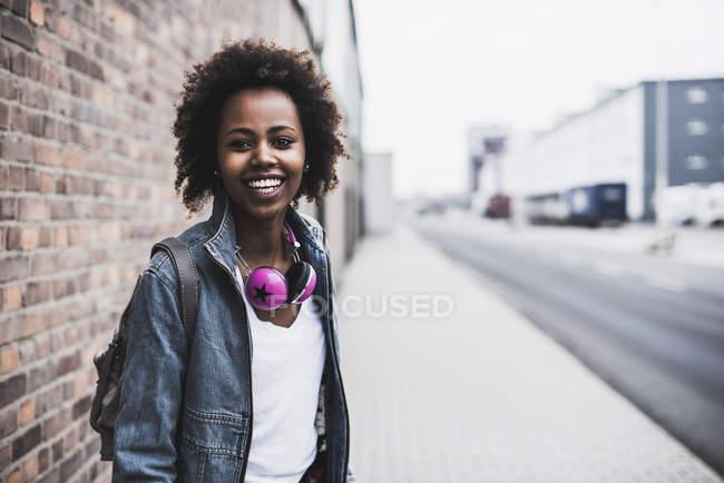Mujer joven sonriente con auriculares y mochila de pie en el pavimento - foto de stock