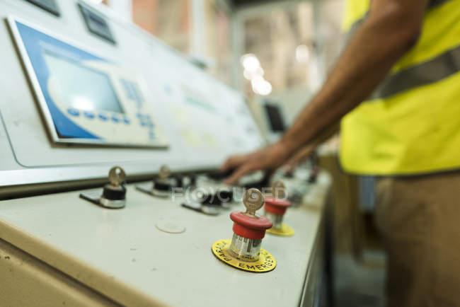 Primo piano dell'operaio nella fabbrica di cemento premendo il pulsante sul pannello di controllo — Foto stock