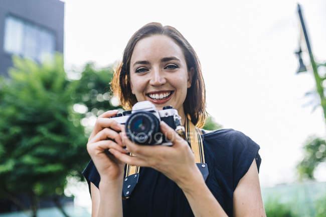 Портрет улыбающейся женщины с камерой в руках — стоковое фото