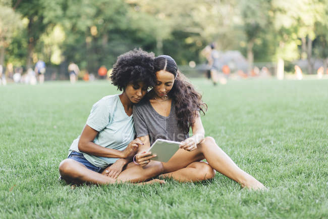 Two best friends sitting on meadow of park and using mini tablet — Stock Photo