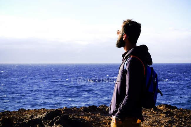 Homme avec sac à dos debout sur la plage et regardant la mer — Photo de stock