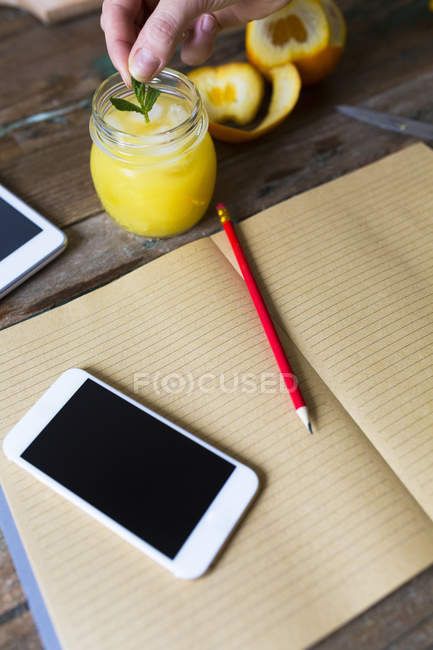 Cropped view of human hand putting mint leaves to juice near blank notebook and smartphone — Stock Photo