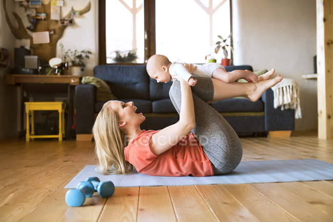 Happy mother lifting up baby at home while lying on mat — Stock Photo
