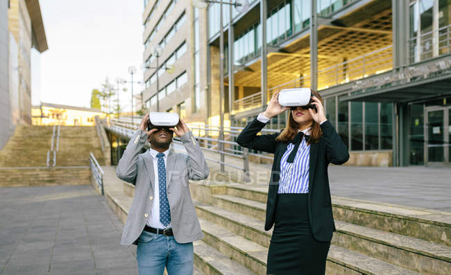 Young businessman and businesswoman using VR goggles next to office building — Stock Photo
