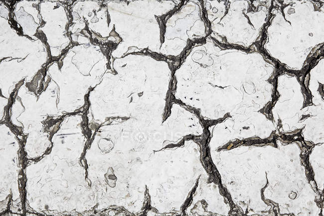 Close-up of Cracks in grey tarmac surface — Stock Photo