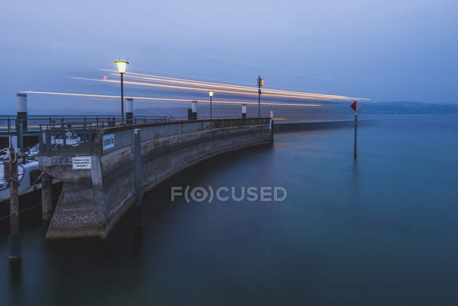 Ferryboat by the pier in evening dusk, motion blur — Stock Photo