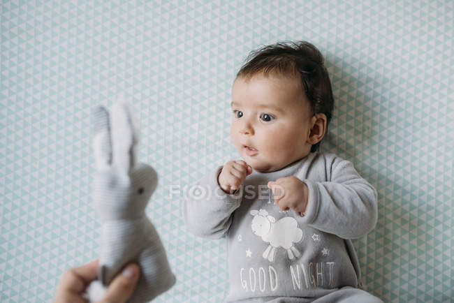Baby girl lying in crib looking at hand holding a stuffed rabbit — Stock Photo