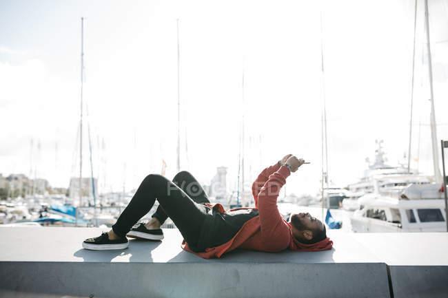 Испания, Барселона. Портрет молодого черного парня в повседневной одежде, лежащего в передвижном положении, с лодками на заднем плане . — стоковое фото