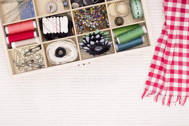Kit em tecido branco com lenço vermelho e branco quadriculado de costura — Fotografia de Stock