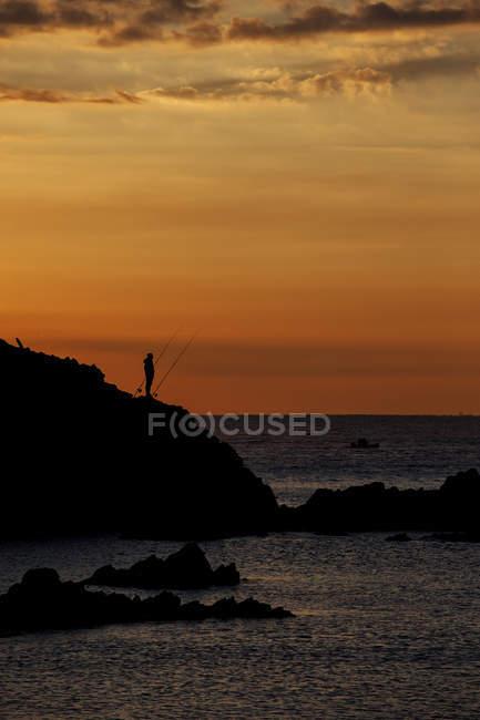 España, Costa Brava, Blanes, pescador solitario y silueta de roca de Sa Palomera al amanecer junto al mar Mediterráneo - foto de stock