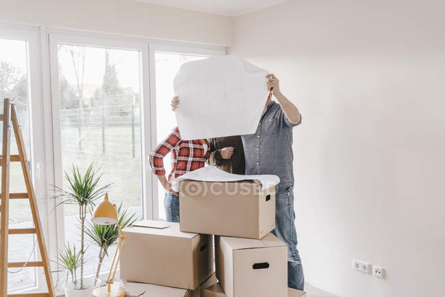 Couple and architect looking at construction plan in new home — Stock Photo