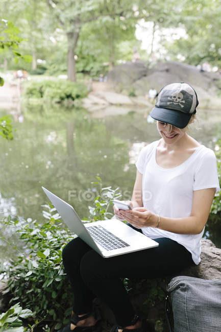 Молода жінка, використовуючи ноутбук і смартфон, сидячи в park, Манхеттен, Нью-Йорк нас — стокове фото