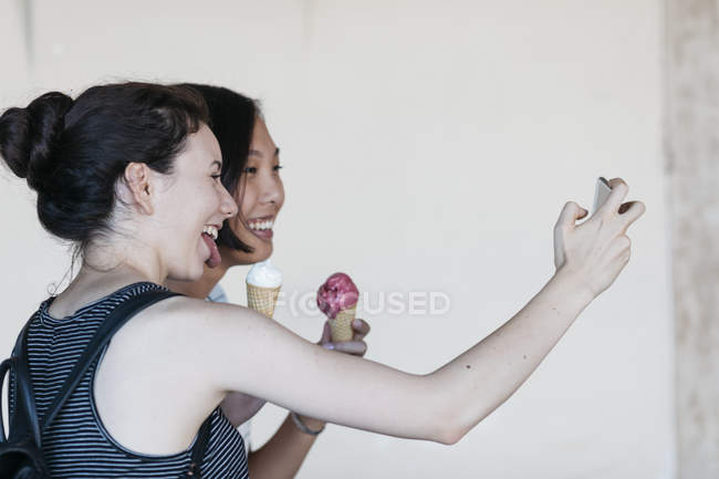 Due giovani donne con coni gelato scattare selfie con smartphone — Foto stock
