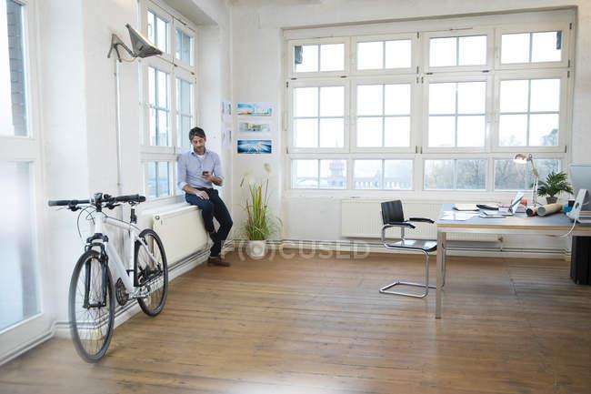 Человек, используя мобильный телефон в современном офисе неофициальных — стоковое фото