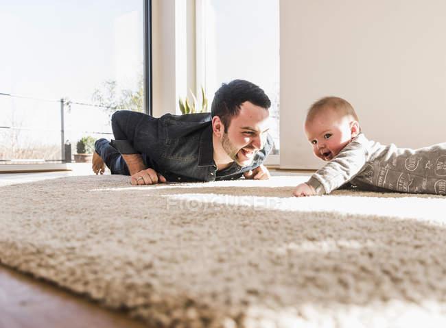 Батько та дитина сина, граючи обходу на килим на дому — стокове фото