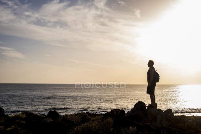 Silhueta de homem em pé em frente ao mar ao pôr do sol — Fotografia de Stock