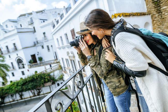 Spagna, Andalusia, Vejer de la Frontera, Giovani donne in viaggio che scattano foto con una macchina fotografica — Foto stock