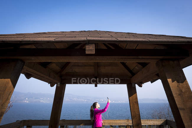 Женщина в спортивной одежде делает селфи на смотровой террасе у моря — стоковое фото