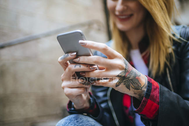 Closeup of tattooed woman hands with smartphone — Stock Photo