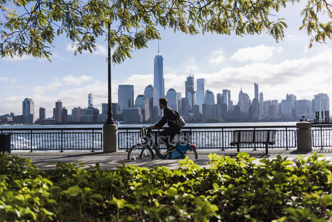 Человек на велосипеде на набережной Нью-Джерси с видом на Манхэттен, США — стоковое фото