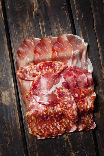 Крупным планом вид ломтики салями и ветчина на деревянные поверхности — стоковое фото