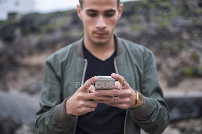 Giovane uomo, leggendo il messaggio di testo — Foto stock