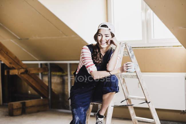Портрет молодой женщины, сидящей на лестнице с чашкой — стоковое фото