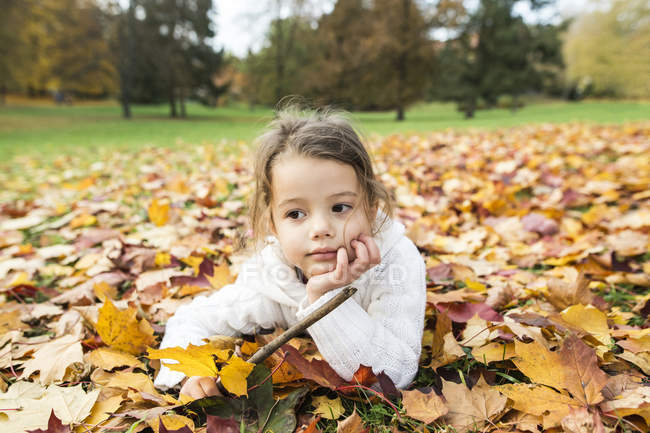 Front view of girl lying in autumn leaves — Stock Photo