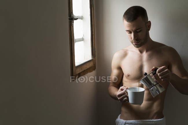 Man gießt Kaffee in Tasse stehen im Dachgeschoss am Fenster — Stockfoto