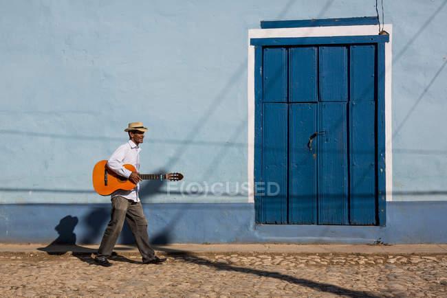 Musicista che cammina con la chitarra in strada di Trinidad, Cuba — Foto stock
