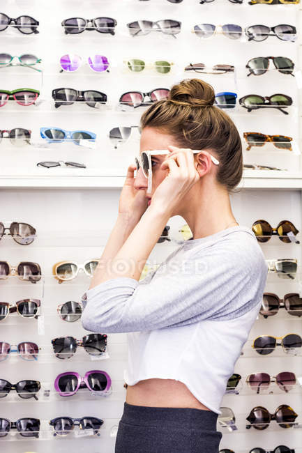 Woman putting on sunglasses — Stock Photo