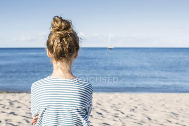 Girl standing on beach and looking at view — Stock Photo