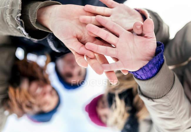 Asturie, Spagna, tre amici che si uniscono le mani nella neve — Foto stock