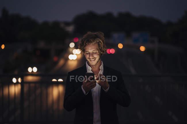 Empresário em uma ponte à noite usando telefone celular — Fotografia de Stock