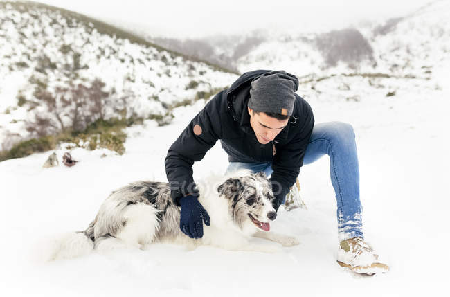 Asturias, Spain, young man stroking his dog in the snow — Stock Photo