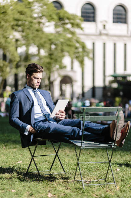 Businessman sitting on garden chair — Stock Photo