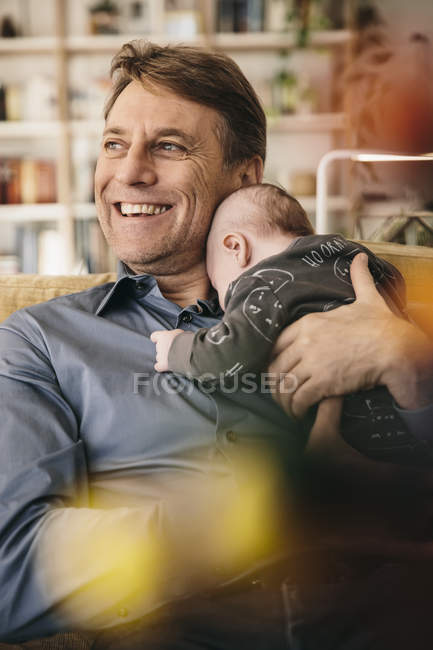 Père heureux avec bébé nouveau-né assis sur le canapé à la maison — Photo de stock