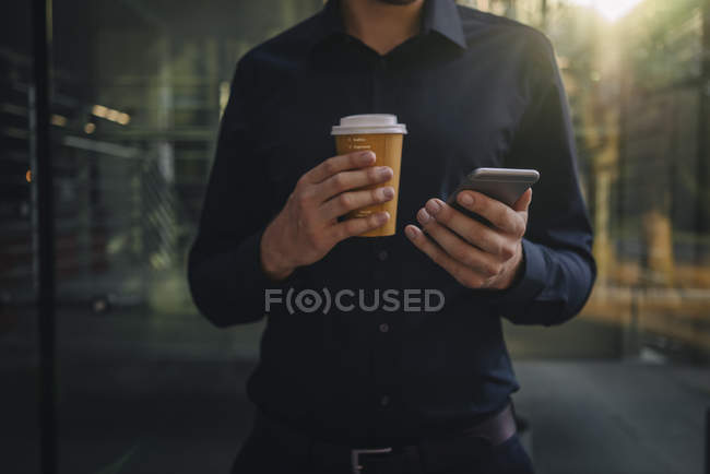 Cropped view of man holding smartphone and disposable cup — Stock Photo