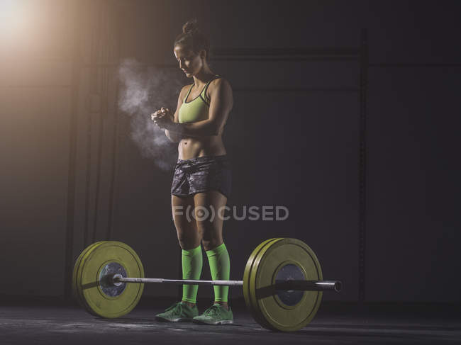 Woman preparing to lift barbell — Stock Photo