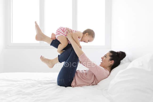 Mom is raising her baby on her legs lying on white bed linen, smiling — Stock Photo