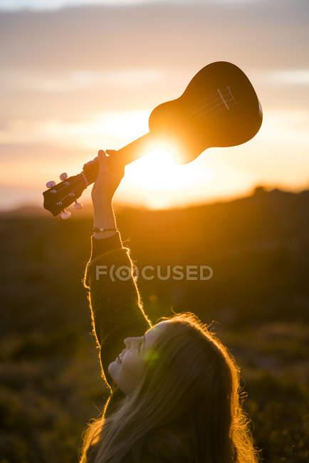 Woman holding up ukulele in nature — Stock Photo