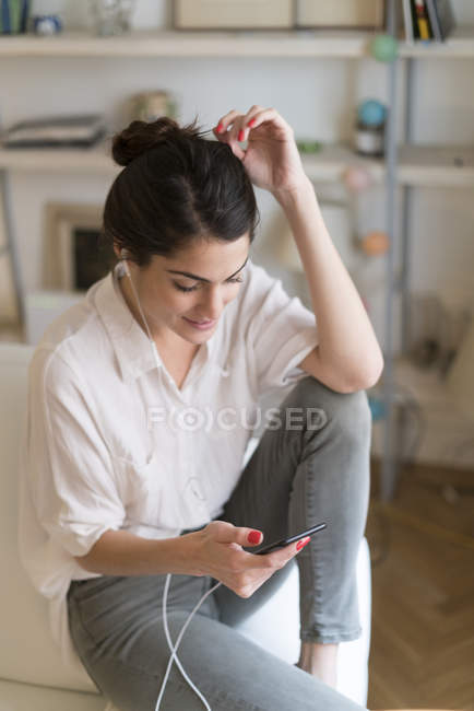 Woman on couch listening music with earphones and smartphone — Stock Photo