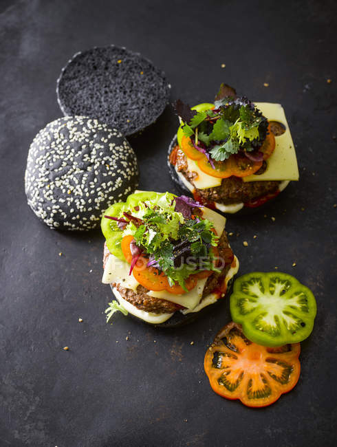 Black Bun Burgers with greens and tomato slices on slate — Stock Photo