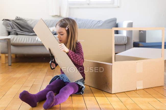 Девушка возится с картонной коробкой дома — стоковое фото